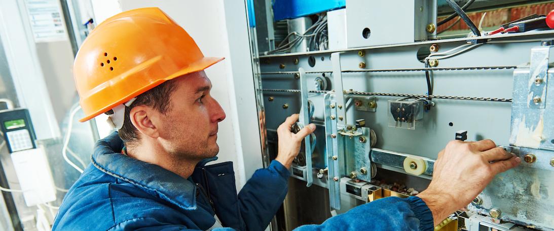 technician worker adjusting elevator mechanism of lift