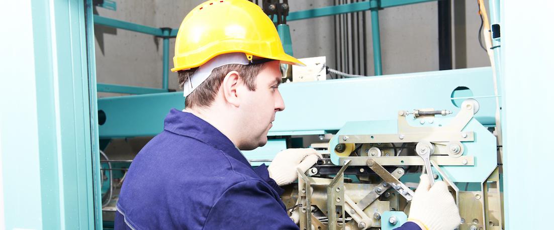 elevator technician working on adjusting elevator mechanism of lift with spanner